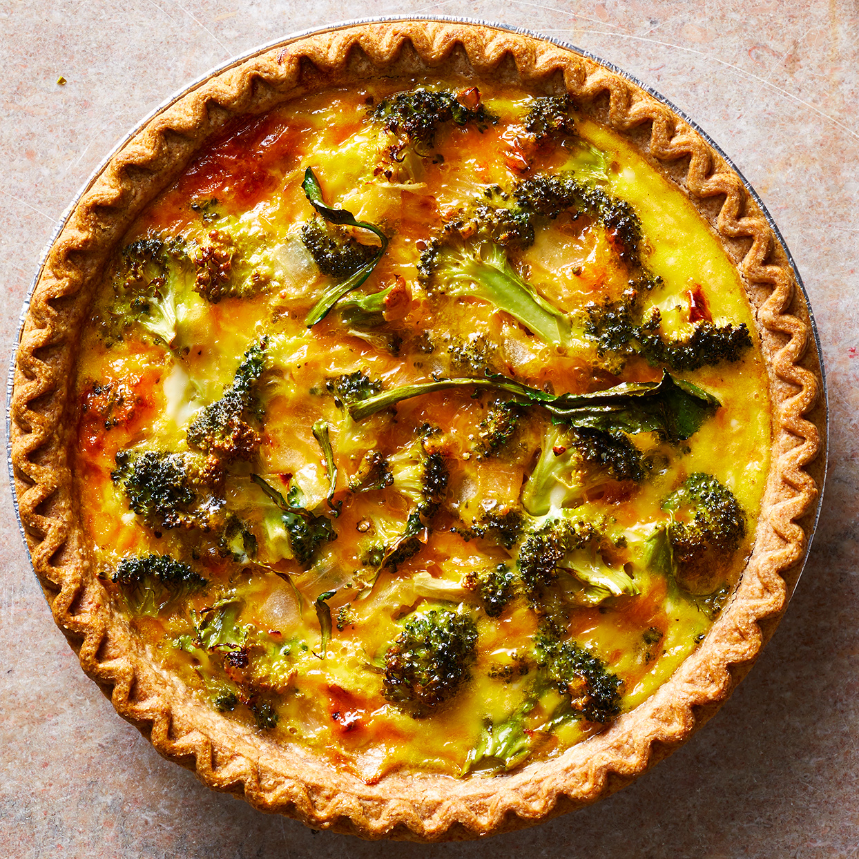 This easy, cheesy broccoli quiche gets its creamy texture from evaporated milk. It's also a great recipe to make ahead: simply reheat before serving or cut into slices and reheat each morning for breakfast. Using pre-cut microwaveable broccoli cuts down on prep time, but if you have broccoli crowns sitting around, go ahead and use those up. Just be sure to cook the broccoli until it's just barely tender or the final dish will have overcooked, soggy broccoli.