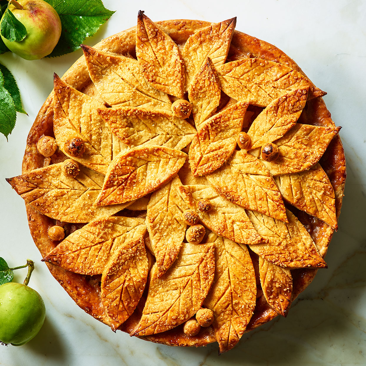 This homemade apple pie recipe has a simple and classic flavor, with fresh apples, spices and butter that's been sizzled until it's brown and nutty. The top crust is where you have the opportunity to add a touch of pizazz. Here we suggest cutting the dough into leaf shapes for an autumnal motif, but you could cut any shape you want.