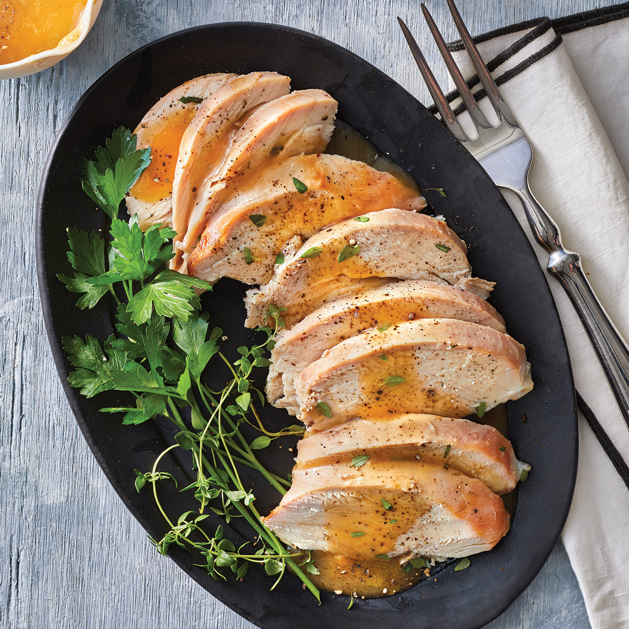Depart from the expected roasted whole turkey for Friendsgiving dinner, and serve this succulent, slow-cooker turkey breast instead. You'll delight guests with a new dish and also save yourself hands-on time and effort. As a bonus on Turkey Day, this recipe leaves your oven free for stuffing and casseroles. If whole turkey breast isn't available, ask your butcher to cut up a whole turkey and give you the whole turkey breast. To make this recipe gluten free, use gluten-free Dijon. For a pretty presentation, serve with fresh thyme and cilantro sprigs.