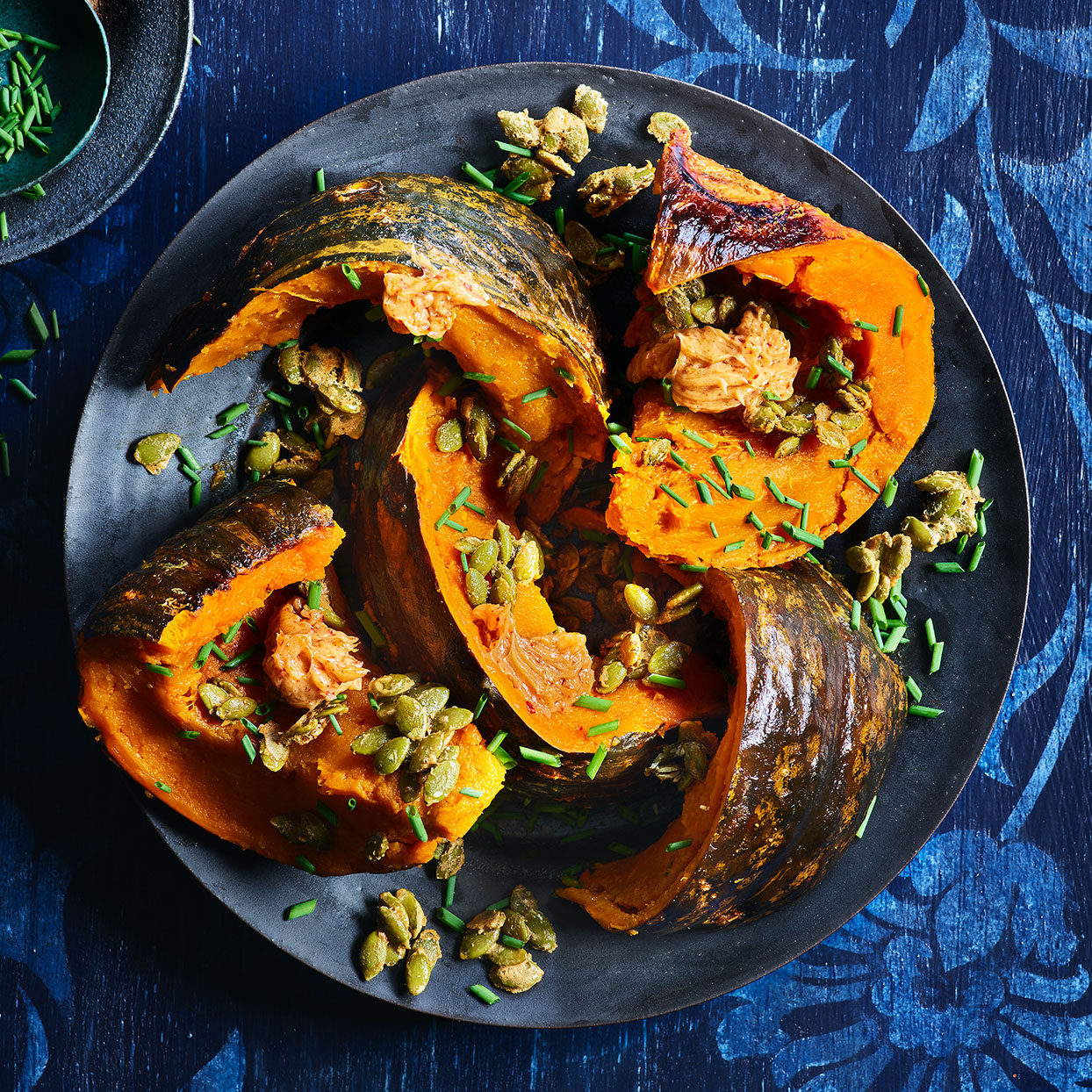 Ever wondered how to cook kabocha squash without ruining your knife? Roasting it whole softens its armor and creates nutty, complex flavor inside. Topped with a savory butter sauce and sweet pumpkin seeds, this Thanksgiving vegetable recipe creates a superstar.