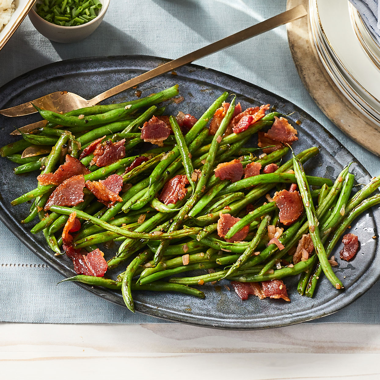 Cooking bacon and green beans on a sheet pan together simplifies holiday meal prep. Red-wine vinegar and lemon juice provide a balanced, bright flavor.