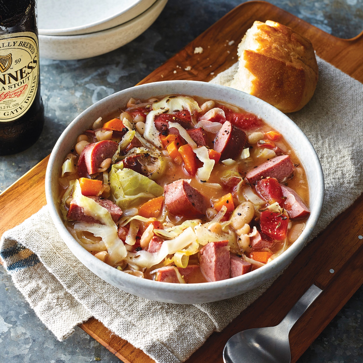 The abundance of springy sausage, soft beans and tender cabbage packed into this slow-cooker recipe means that each bite is loaded with varied texture. To make this recipe gluten free, use gluten-free sausage. Serve with bread and Guinness, if desired.