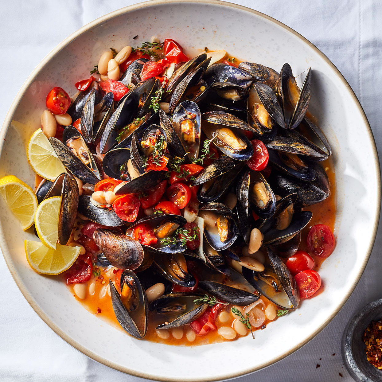 Cooking mussels may seem intimidating, but here we've made it quick and easy. We've added white beans to turn this classic mussels-in-white-wine-sauce dish into a heartier weeknight meal. Serve with whole-grain crusty bread to sop up the flavorful broth.
