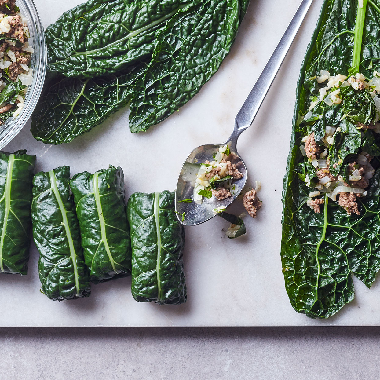 For a quick version of stuffed grape leaves, we've put all the flavors of a traditional dolma recipe into a cooked filling that's simply wrapped in blanched kale leaves—no need to simmer for hours.